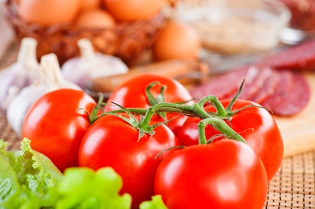 foods (tomatoes, lettuce, garlic, spices,sausage, eggs)