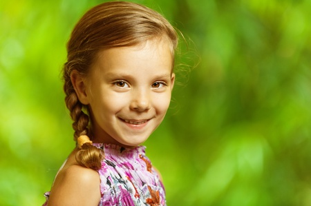 portrait of beautiful smiling girl with pigtail to green park background