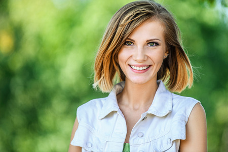 Photo for Portrait of smiling beautiful young woman close-up, against green of summer park. - Royalty Free Image
