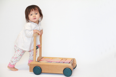 Photo for Japanese baby girl pushing a cart (1 year old) - Royalty Free Image