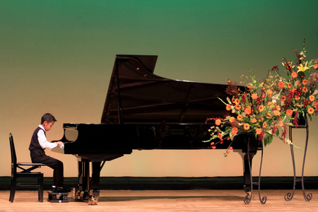 Photo for Japanese boy playing piano on stage (second grade at elementary school) - Royalty Free Image