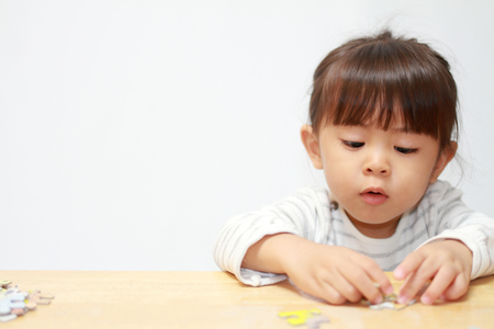 Photo pour Japanese girl doing jigsaw puzzle (3 years old) - image libre de droit