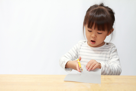 Photo pour Japanese girl cutting paper with scissors (3 years old) - image libre de droit