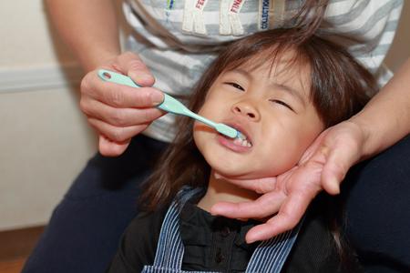 Foto de Japanese girl whose teeth are brushed by her mon (3 years old) - Imagen libre de derechos