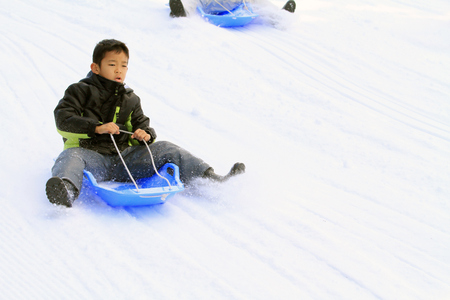 Photo for Japanese boy on the sled (second grade at elementary school) - Royalty Free Image