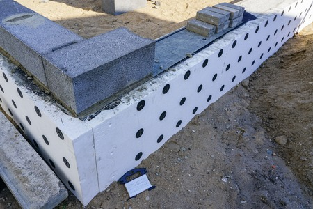 Photo pour Concrete foundation and foundation thermal insulation of a new house, view of construction site in preparation process - image libre de droit