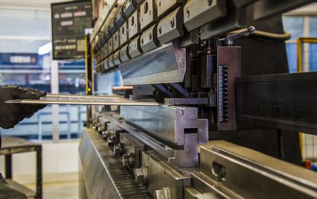 Photo pour worker operating metal press machine at workshop. - image libre de droit