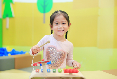 Photo for Asian kid girl having fun with Toys, musical instruments - Royalty Free Image