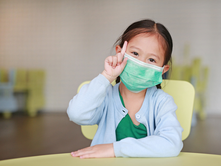 Photo pour Cute little Asian child girl wearing a protective mask with showing one forefinger sitting on kid chair in children room - image libre de droit