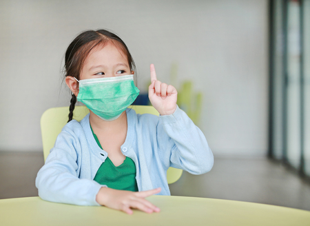 Foto de Cute little Asian child girl wearing a protective mask with showing one forefinger sitting on kid chair in children room. - Imagen libre de derechos