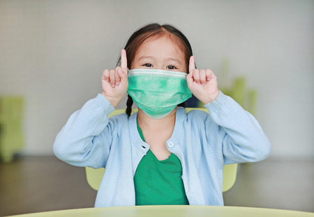 Photo pour Cute little Asian child girl wearing a protective mask with showing two forefingers sitting on kid chair in children room. - image libre de droit
