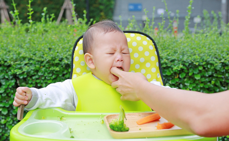 Foto de Close-up infant baby boy sitting on kid chair eating with something stuck in his mouth and mother help to keep out. - Imagen libre de derechos