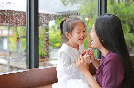 Photo pour Asian mother and her daughter playing with love near a window while raining day. - image libre de droit