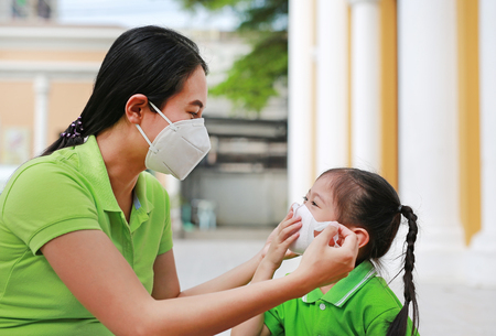 Photo pour Asian young mother wearing protective mask for her daughter while outside to against PM 2.5 air pollution in Bangkok city. Thailand. - image libre de droit
