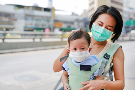 Foto de Asian mother carrying her infant baby by hipseat outdoor with wearing a protection mask against PM 2.5 air pollution in Bangkok city. Thailand. - Imagen libre de derechos