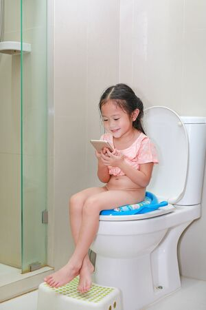 Foto de Adorable little Asian child girl playing smartphone while sitting on toilet. - Imagen libre de derechos
