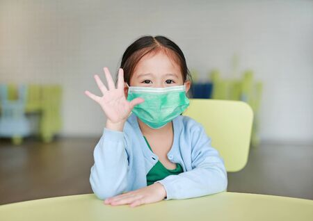 Photo pour Little Asian child girl wearing a protective mask with showing five fingers sitting on kid chair in children room. - image libre de droit