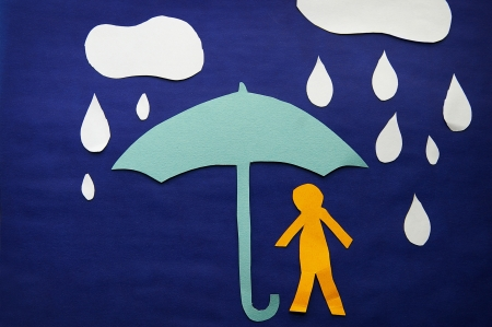 paper cutout man under an umbrella in the rain