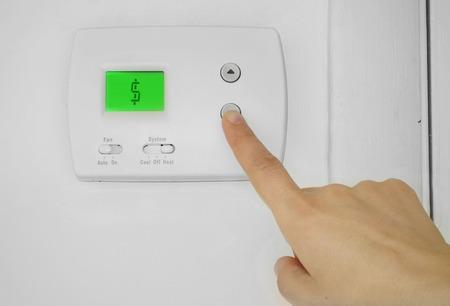 Foto de Person adjusting a wall thermostat with dollar sign symbol on the display - Imagen libre de derechos