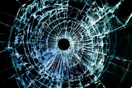 Foto de Bullet hole in a shattered piece of glass - Imagen libre de derechos