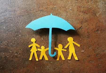 Foto de Paper family of four under a paper cutout umbrella - Imagen libre de derechos