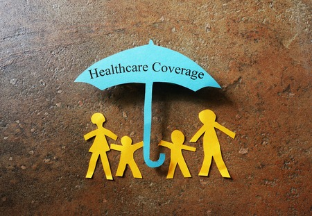 Photo pour Paper family of four under a  Healthcare Coverage umbrella - image libre de droit
