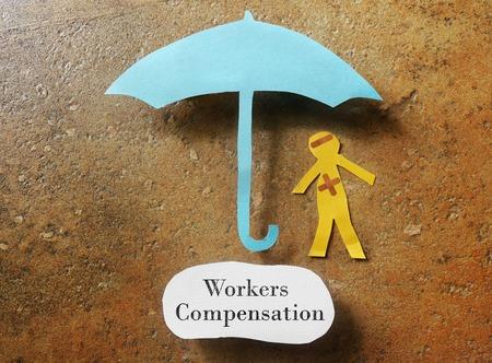Foto de bandaged paper man under umbrella with Workers Compensation note below - Imagen libre de derechos