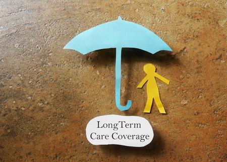 Photo pour Paper person under an umbrella with Long Term Care Coverage text -- elder care insurance concept - image libre de droit