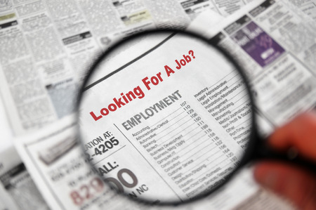 Photo pour Magnifying glass over Jobs section of newspaper classifieds - image libre de droit