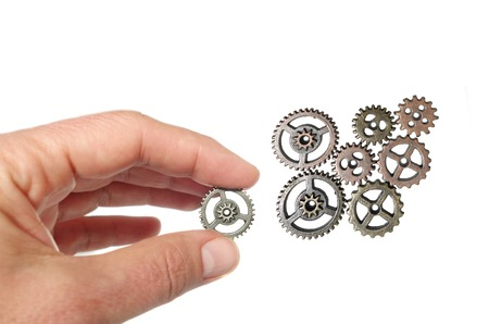 Photo for Hand placing a gear together with others, isolated on white - Royalty Free Image