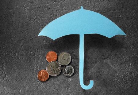 Foto de Coins under a paper umbrella -- financial security or retirement savings concept - Imagen libre de derechos