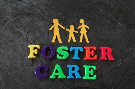 Foto de Paper family with Foster Care letters - Imagen libre de derechos