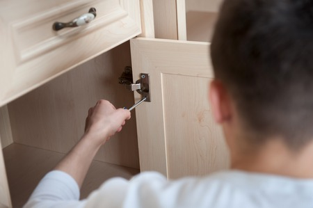Young smiling caucasian handsome man fixing wooden furniture by screwdriver from behind, selective focus