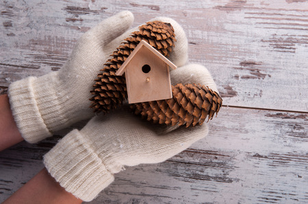 Christmas tree toys like pine cones and birdhouse in hands dressing in white mittens on wooden table top view with copy place