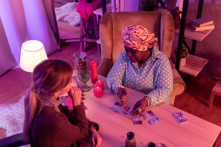 Reading details. African american plump fortune-teller wearing a huge ring explaining the details to the client