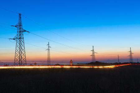 Foto de Pylons and electrical power lines at dusk with traffic lights in front - Imagen libre de derechos