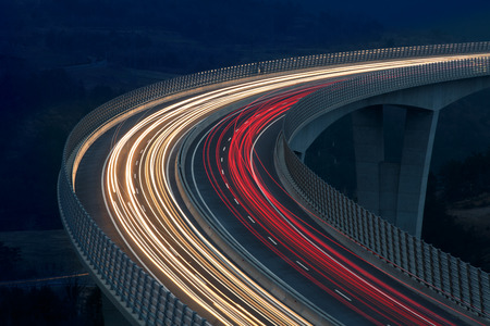 Photo pour Blurred lights of vehicles driving on a tall viaduct with wind barriers, long exposure - image libre de droit