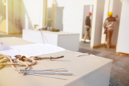 Photo for Building plan, eye bolt and screws on plasterboard panels with workers in background - Royalty Free Image