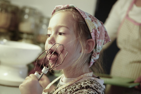 Photo pour Little girl licking chocolate off the mixer beater after mixing dough for birthday cake. Permissive parenting, learning through experience, child inclusion, homemade food concept. - image libre de droit