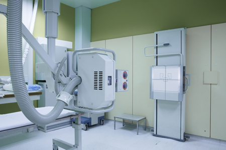 Foto per X-ray room in a hospital ER operating room with a classic ceiling-mounted x-ray system. Modern medical equipment, interventional medicine and healthcare concept. - Immagine Royalty Free