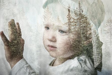 Foto de Little boy daydreaming, looking out the window at nature, thinking about it. Double exposure of child portrait and forest landscape. Hope, dreaming, back to nature, future, sustainability concept. - Imagen libre de derechos
