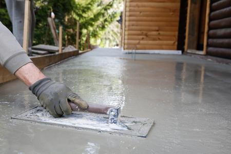 Foto de Mason leveling and screeding concrete floor base with square trowel in front of the house. - Imagen libre de derechos