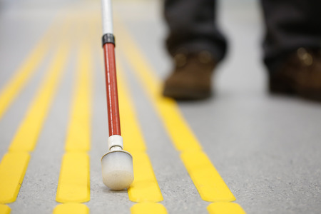 Photo for Blind pedestrian walking and detecting markings on tactile paving with textured ground surface indicators for blind and visually impaired. Blindness aid, visual impairment, independent life concept. - Royalty Free Image