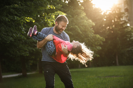 Photo for Devoted father spinning his daughter in circles, bonding, playing, having fun in nature on a bright, sunny day. Parenthood, lifestyle, parenting, childhood and family life concept. - Royalty Free Image