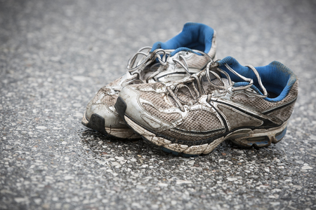 Photo for Worn, dirty, smelly and old running shoes on a tarmac road. Road running, endurance, marathon aftermath and active lifestyle concept. - Royalty Free Image