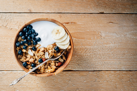 Photo pour Homemade oatmeal granola with peanuts, blueberry and banana in wooden bowl, sunny morning - image libre de droit
