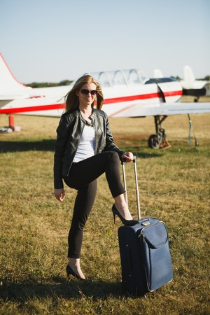 Photo pour Girl with a blue bag near the small aircraft. Concept of woman who returned from travel on private airplane - image libre de droit