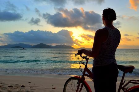 Foto de Girl with a bicycle on the beach admiring the beautiful sunset. Silhouette at twilight. Seychelles island La Digue - Imagen libre de derechos
