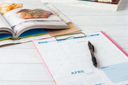 Foto de Monthly calendar and stack of cookbooks. Conceptual image showing meal planning in progress. Shallow depth of field - Imagen libre de derechos