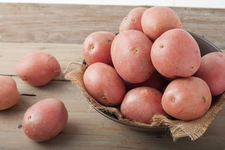 Photo pour large red potatoes in a bowl on wooden background - image libre de droit